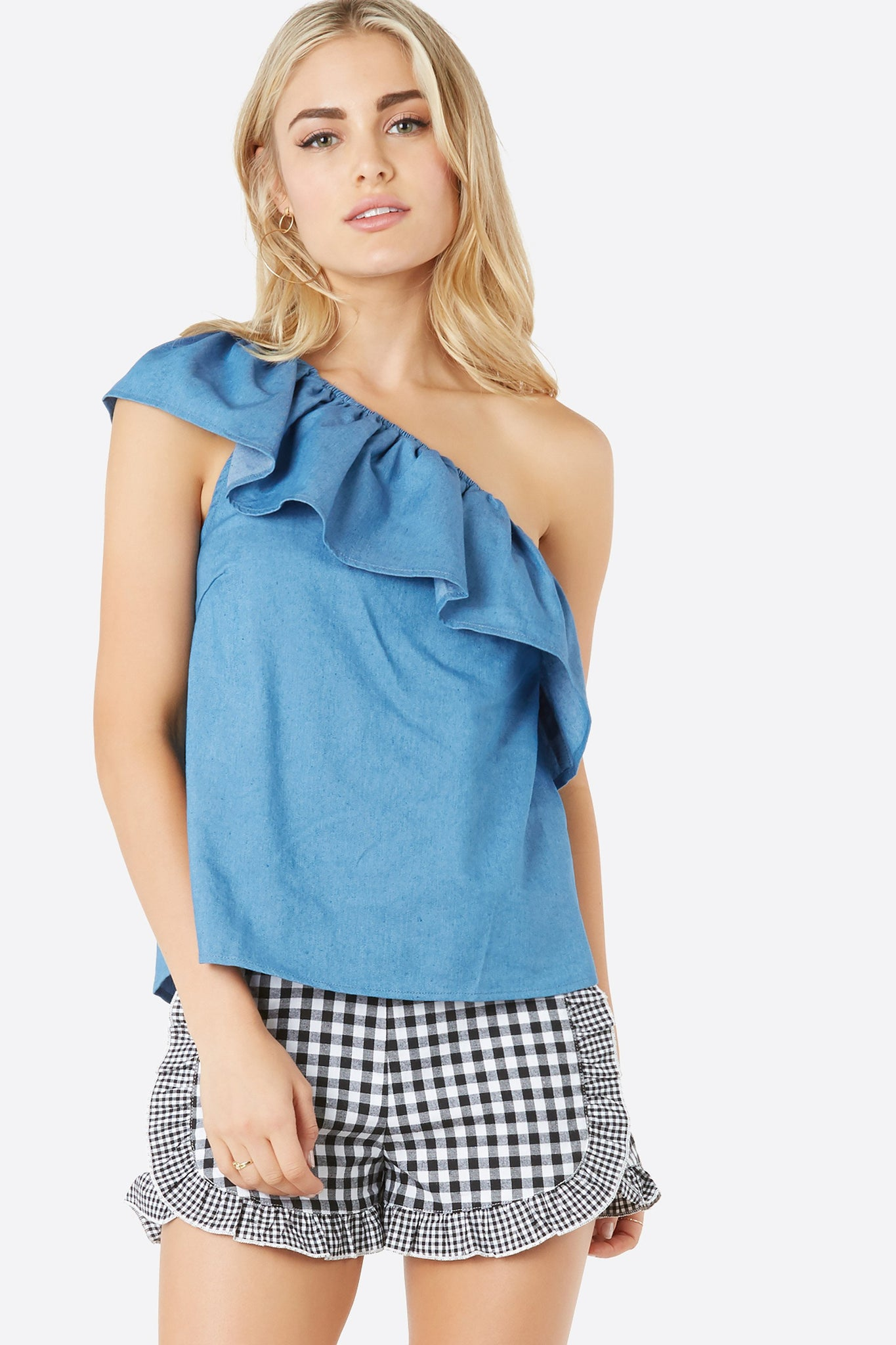 Chic one shoulder top with bold ruffle tier design. Relaxed fit with slightly curved hem finish.
