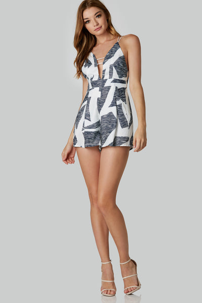 Strappy sleeveless romper with abstract patterns throughout. Overlap hem with cut out and hidden zip for closure in back.