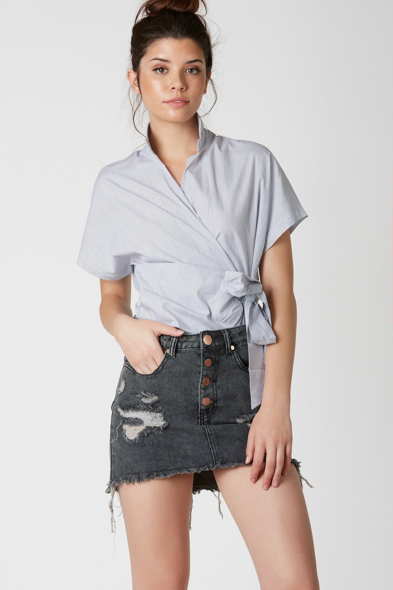 Chic short sleeve blouse with pin stripe patterns throughout. Deep V-neckline with wrap over front and ties for closure.