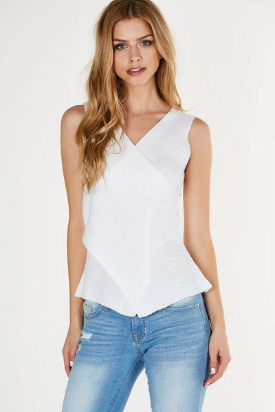 Chic sleeveless top with overlap design. Comfortable ribbed knit material with envelope hem finish.