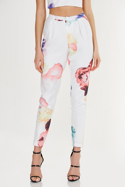 Watercolor floral print high rise tapered trousers with ankle grazer hemline, two back pockets, and front zipper/metal clasp closure.