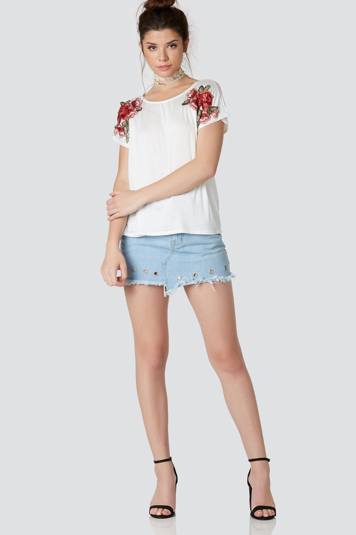 Casual round neck T-shirt with cap sleeves and relaxed fit. Hi-low hem with bold floral patches on each shoulder.