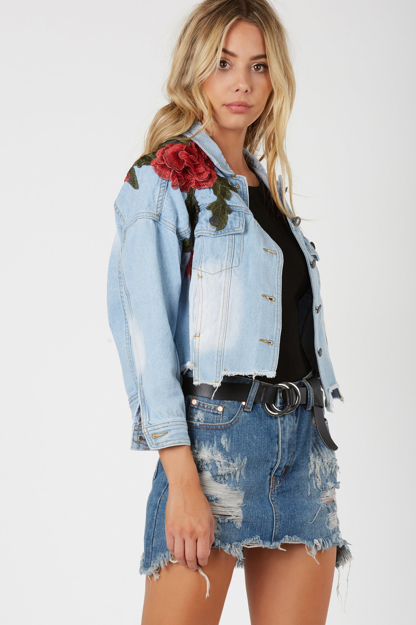 Stylish denim jacket with bold floral patches throughout. Fadded wash with uneven, raw hem finish for a vintage vibe.