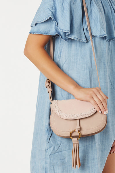 Trendy structured convertible bag with faux leather body and contrast suede finish. Bold ring hardware detailing with tassel attached. Dettachable strap to wear as a crossbody and fanny pack.