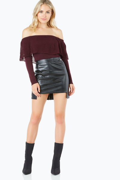 High waisted vegan leather mini skirt with faux buttons and back zip closure. Uneven hem with front seam detailing.