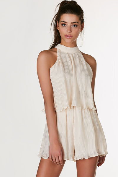 Sleeveless mock neck romper with tiered design and pleated finish. Cut out back with tie and hidden zip closure.
