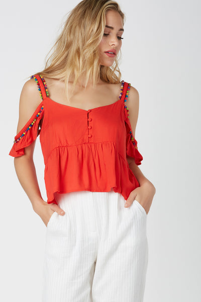 Fun V-neck top with cold shoulder design. Flirty ruffled sleeves with buttons in front. Colorful pom-pom trimming at shoulders for added detail.