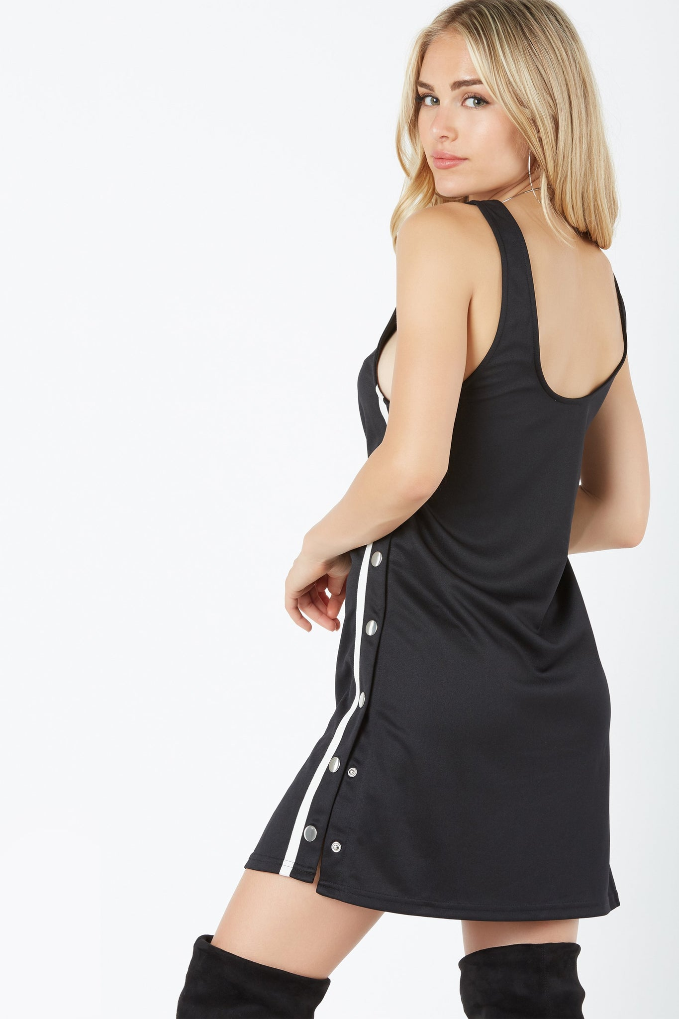 Sleevess tennis style dress with trendy snap button detailing down each side. U-neckline with straight hem finish.