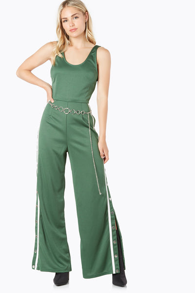 Trendy sleeveless jumpsuit with back zip closure. Wide leg fit with snap buttons down each side.