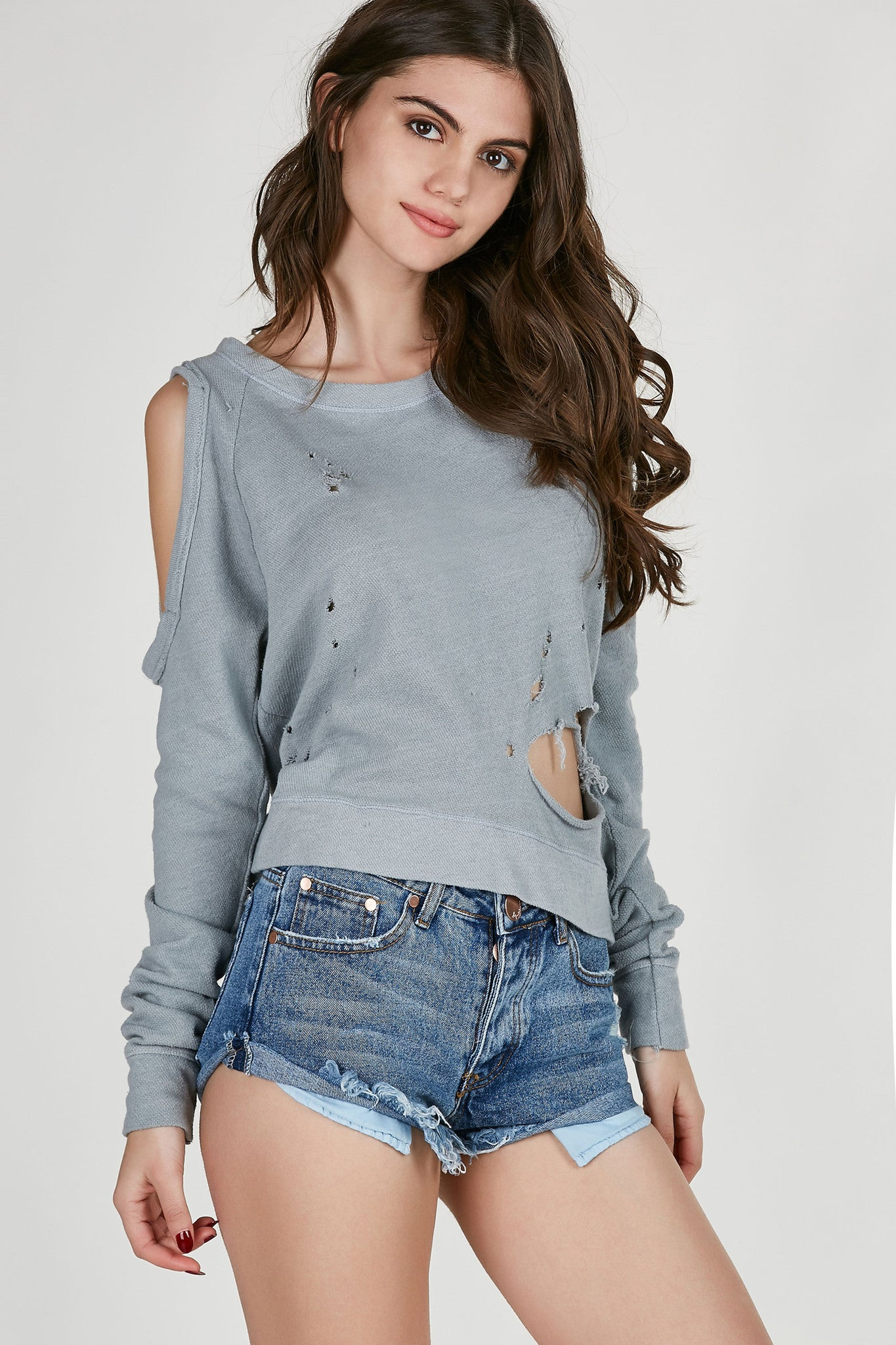 Long sleeve textured sweater with bold cold shoulder cut outs. Distressed throughout the front with relaxed fit.