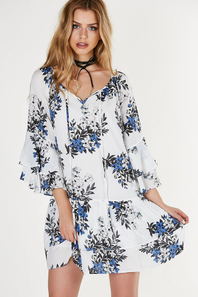 Oversized floral printed tunic dress with flirty bell sleeves and tiered hem all around. Cut out at neckline with halter neck ties for added detail.