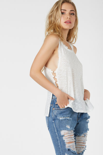Casual round neck sleeveless top with open sides and silver hardware rings for added detail. Frayed edges at top with straight hem finish at bottom.