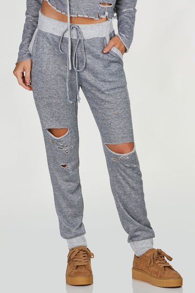 High rise joggers with trendy exposed hem and waistband. Distressing throughout with relaxed fit and side pockets. Comes in a set with matching hoodie sold separately.