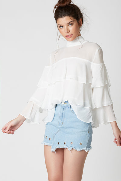 Very chic long sleeve blouse made of sheer lightweight material. Flirty ruffle tier design with mock neckline that ties in back for added detail.