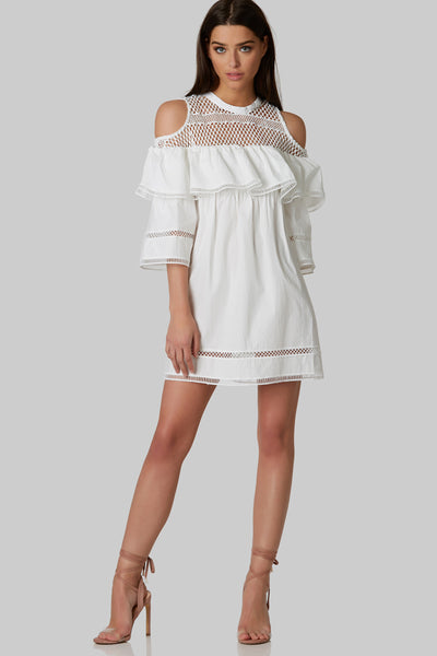 Flirty tunic dress with crocheted design and ruffle detailing. Flowy relaxed fit with one button closure in back and 3/4 open sleeves.