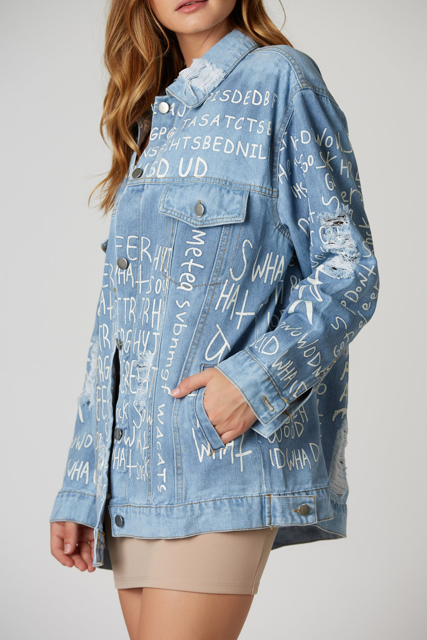 Casual oversized graphic denim jacket with shredded detailing throughout. Side pockets with button closure.