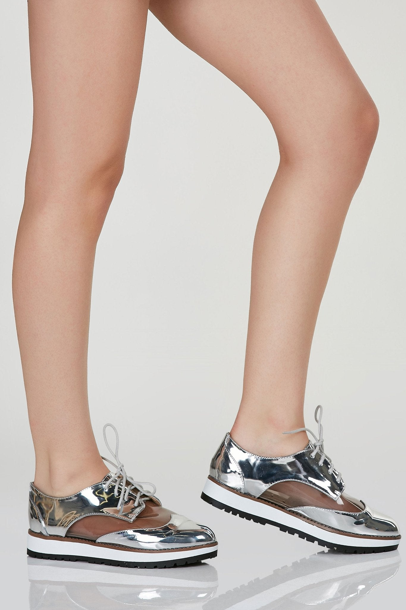 Pointed toe oxfords with classic lace up closure. Metallic finish with contrast clear panels for a peek-a-boo effect.