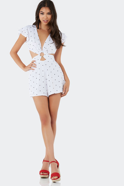 Flirty deep V-neck romper with ruffled cap sleeves and bold cut outs. Ring detailing at center with polka dot print throughout.