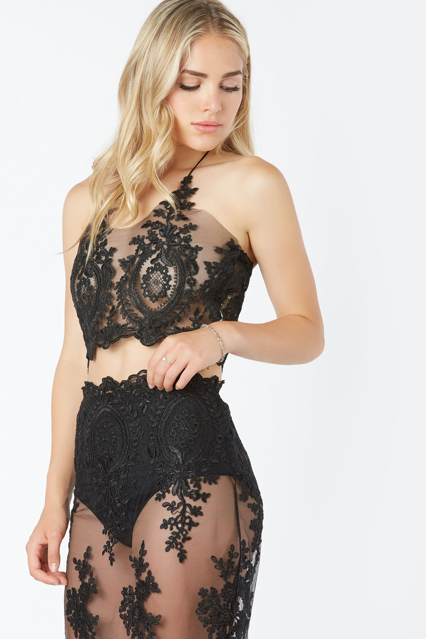Delicate mesh crop top with corded embroidery throughout. Dainty halter tie detailing and back zip closure.