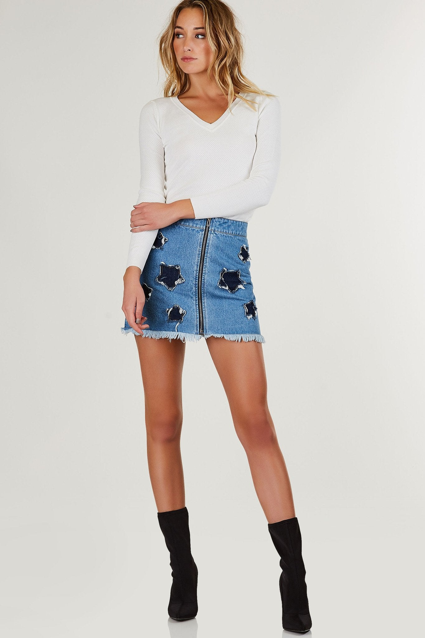 Mid rise denim mini skirt with star shape patches. Front zip closure with straight frayed raw hem.