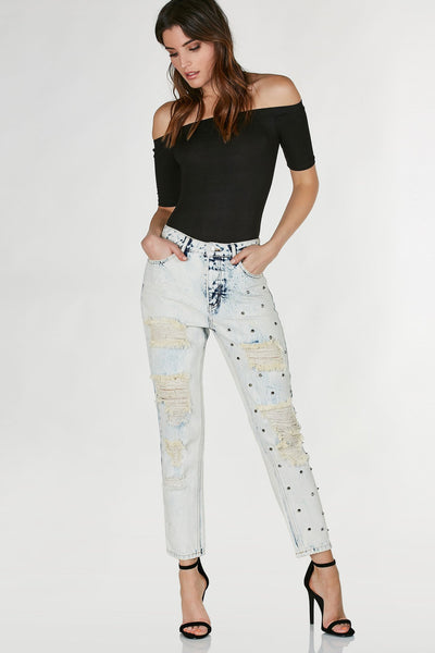 Mid rise distressed boyfriend jeans with vintage light wash and spike stud detailing on one leg.