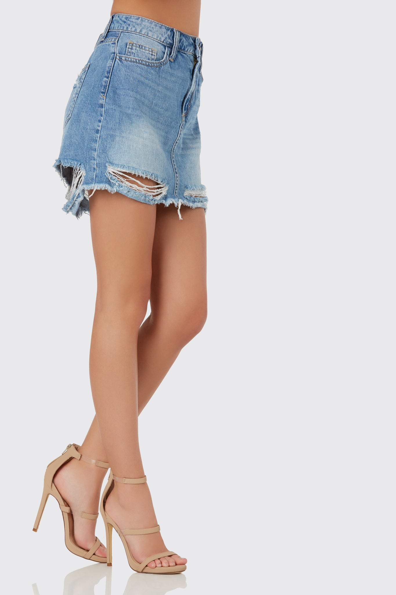 Chic deim mini skirt with distressed detailing throughout. Shredding and frayed hem finish.