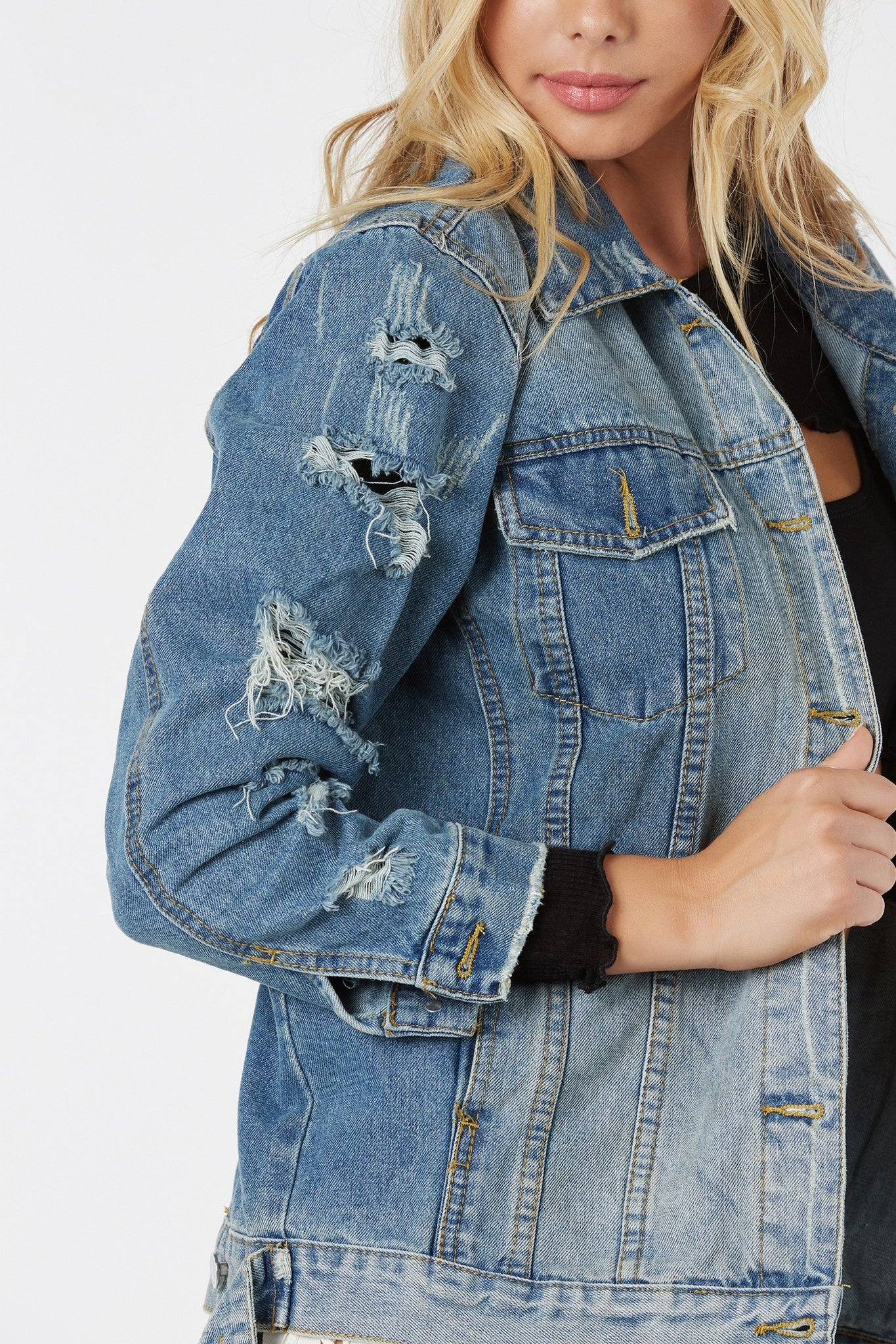 Trendy oversized denim jacket with heavy distressing. Classic button front closure with vintage style wash.