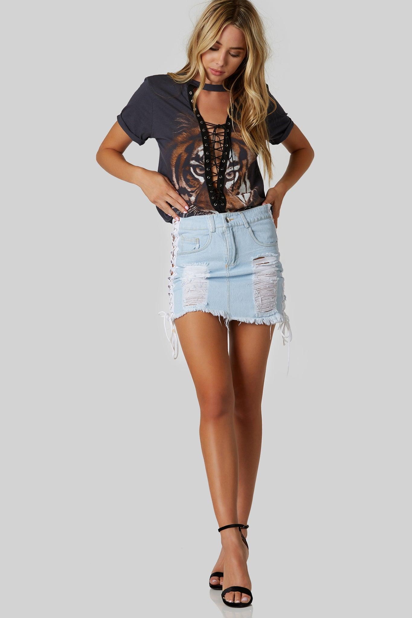 Trendy denim mini skirt with shredded detailing in both front and back. Contrast lace up panels down each side with button and zip closure.