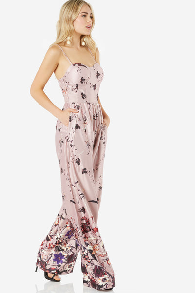 Sleeveless jumpsuit with silky, satin-like finish. Padded bust with sweetheart neckline. Floral print throughout with wide leg fit.