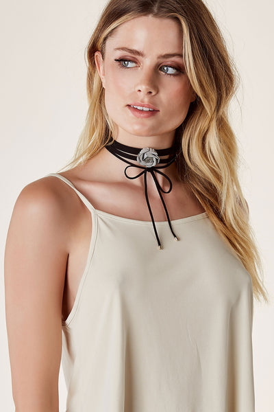Flirty suede choker set. Single band with center rose design and lobster clasp for fit and closure. Classic wrap style choker with gold hardware tips for added detail.