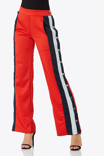 Tear away track pants with front pockets and side metal snap button closures. Elastic waistband for additive comfort.