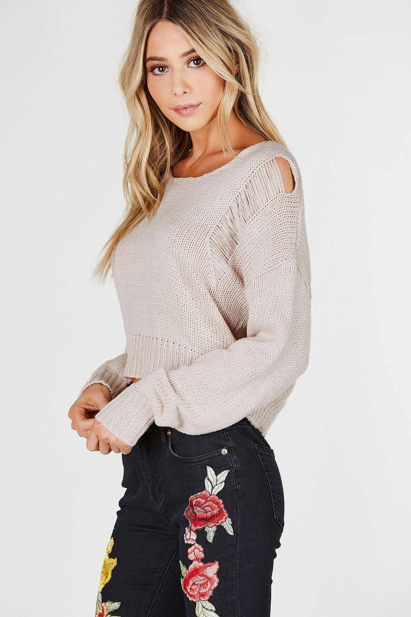 Round neck long sleeve knit sweater with shredded detailing. Cropped with relaxed fit.