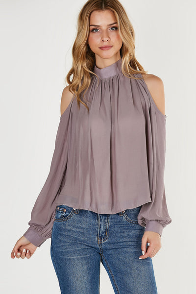 Chic mock neck blouse made of lightweight chiffon material. Long sleeves with cut outs on shoulders and back.
