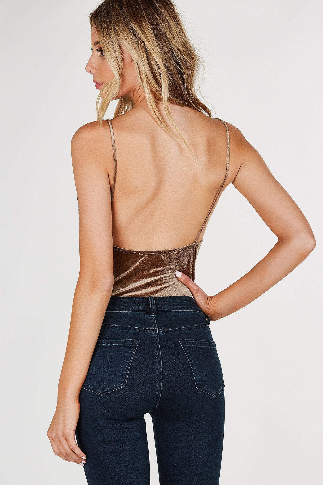 Soft V-neck cami bodysuit with lace trimming at top. Velvet finish with cheeky cut and snap button closure.