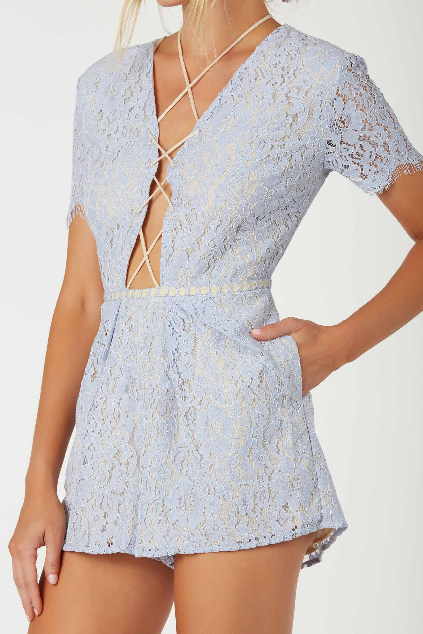 Elgant lace romper with plunging front with lace up design. Eyelash trim at sleeves with back zip closure.