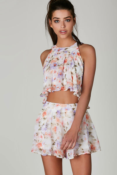 Flirty mock neck sleeveless top with comfortable lining and floral prints throughout. Cropped hem with button closure and keyhold cut out in back.