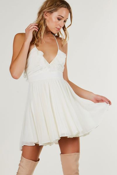 Adorable V-neck mini dress with flared pleated body. Ruffle detailing throughout wit cut out in back with ties for closure. Hidden zipper on one side and full lining.
