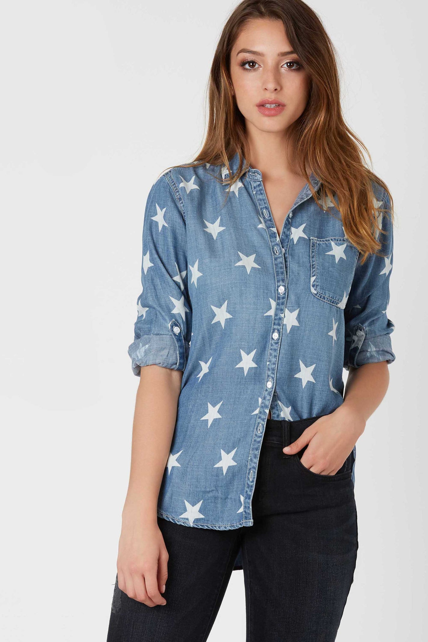 Casual chambray button down top with full length sleeves and classic collared design. Run start patterns throughout with curved hi-low hem.