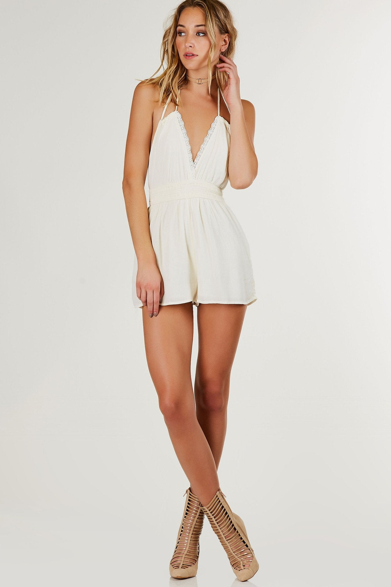 Sleeveless halter romper with adorable crochet trim at V-neckline. Gauze material with flared hem and full lining.