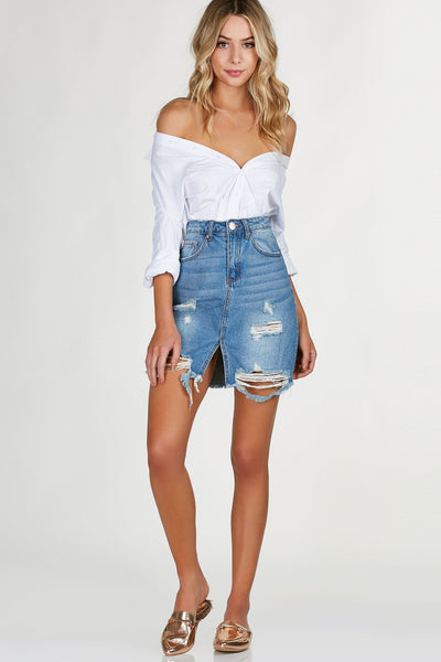 Hi rise denim skirt with trendy distressing and center slit for added detail. Raw hem all around with zip and button for closure.