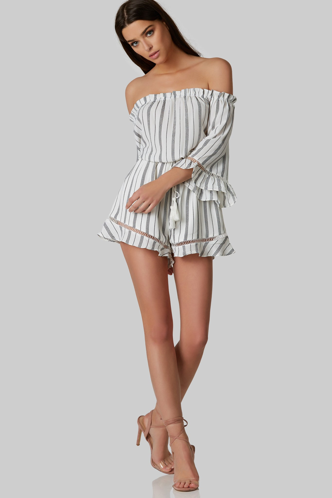 Lightweight stripped romper with cold shoulder. Flowy fit with elastic bands for comfort and fit. Tassel tie around waist with ruffle and intricate lace detailing on long sleeves.