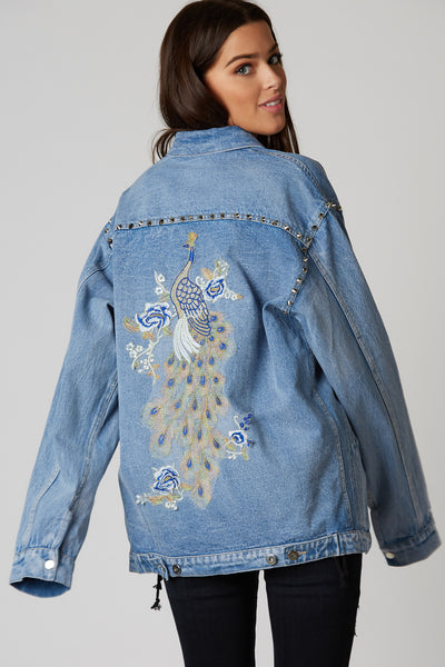Trendy oversized denim jacket with studded detailing.. Vintage vibe with patched peacok design on back.