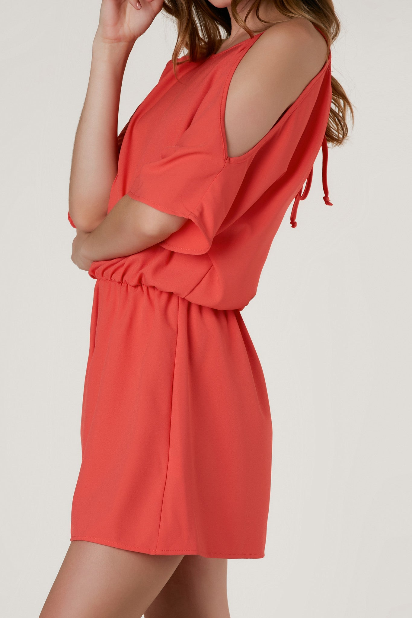 Loose fit cold shoulder romper with cinched waist and cut out detailing in back.