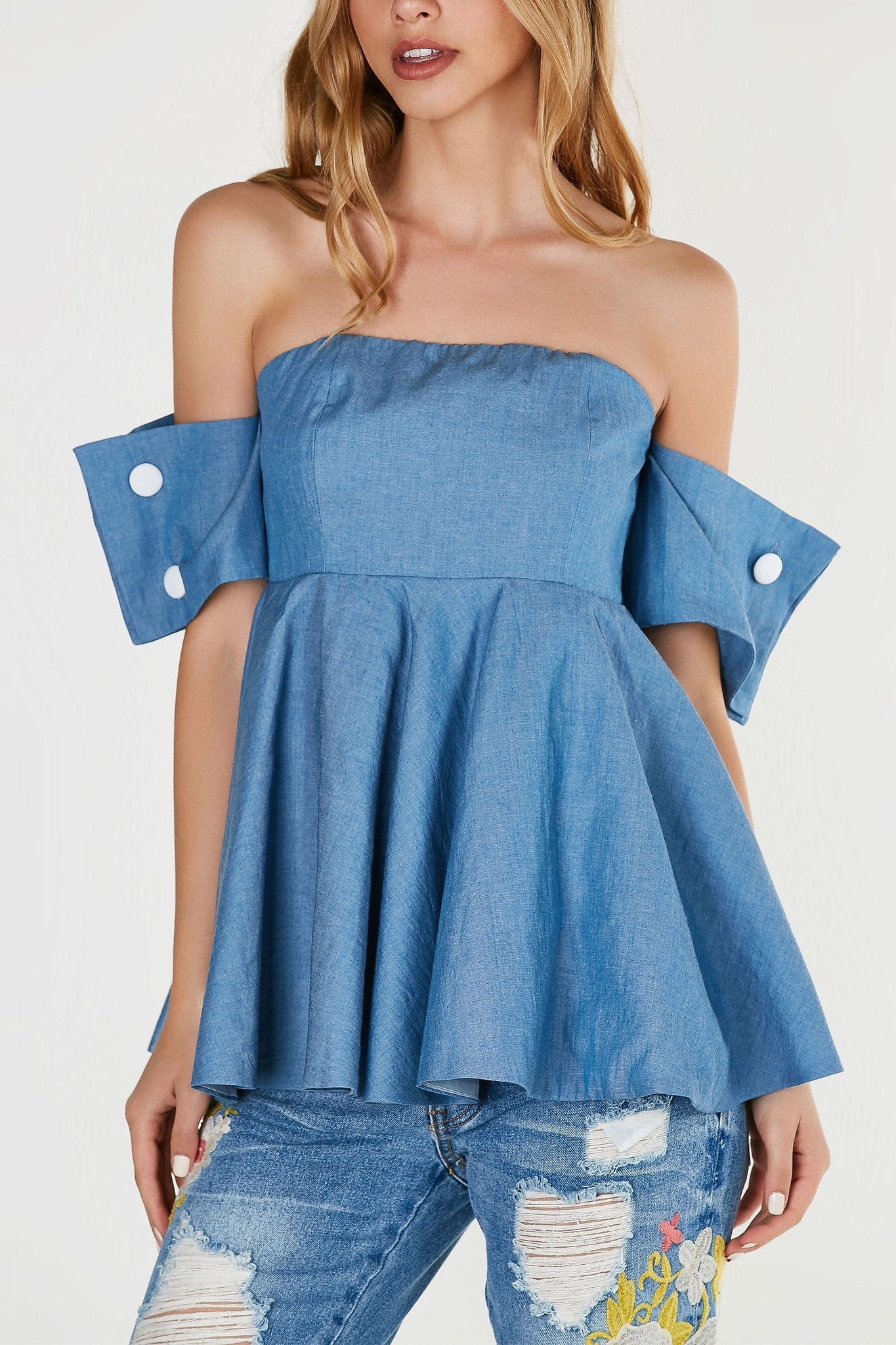 Chic off shoulder top with chambray exterior and smooth lining underneath. Peplum style A-line hem and wrapped sleeves with button closure detailing.