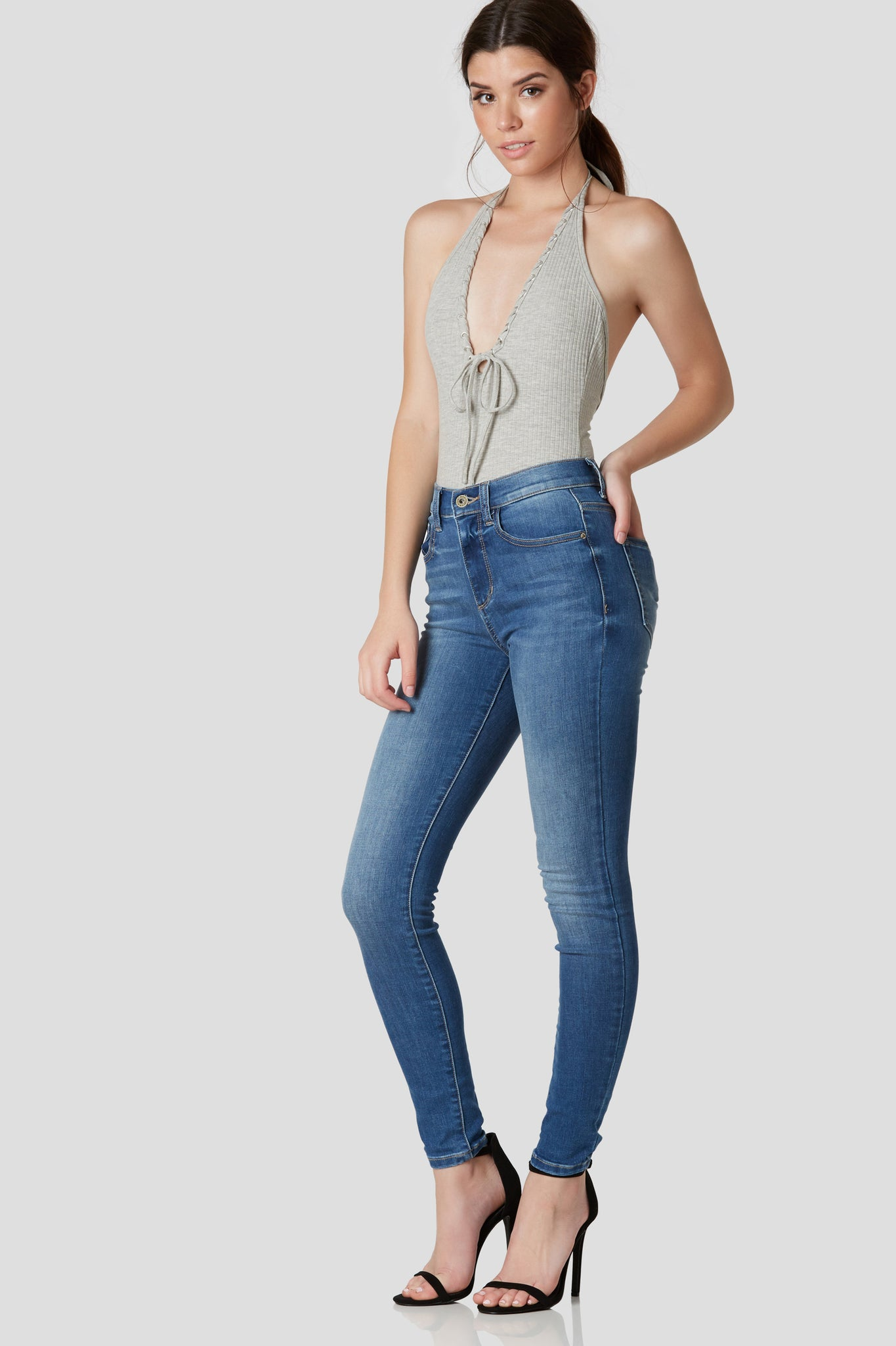Classic blue high waist skinny jeans with stretchy material for flattering fit. 5 pocket design with button and zip closure.