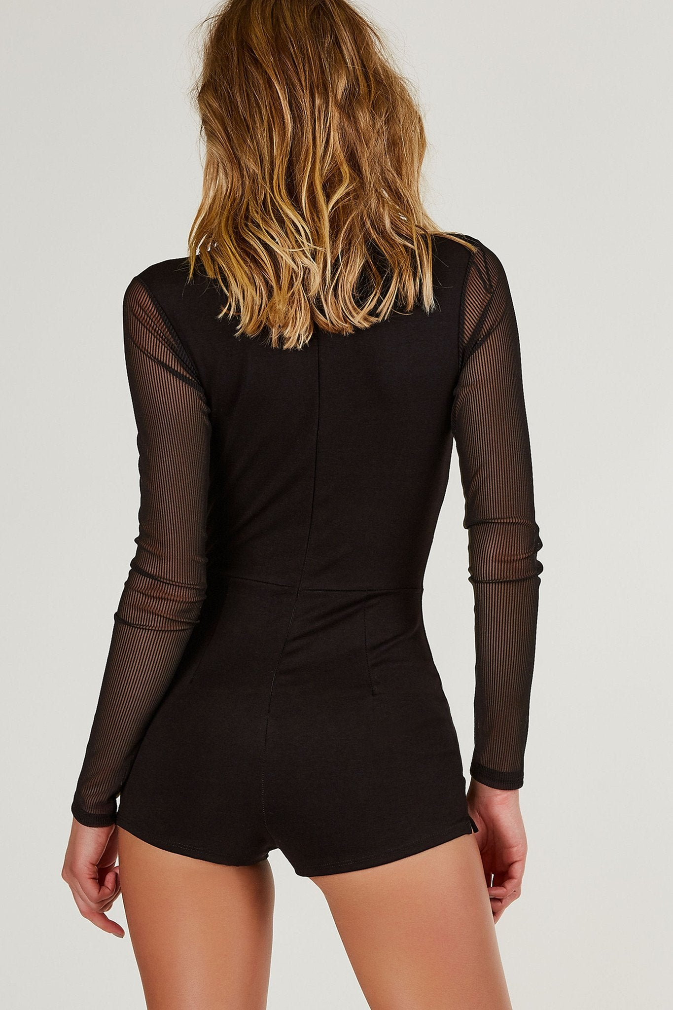 Deep V-neck romper with contrast mesh sleeves. Stretchy material with overall slim fit and hidden zip closure in back.