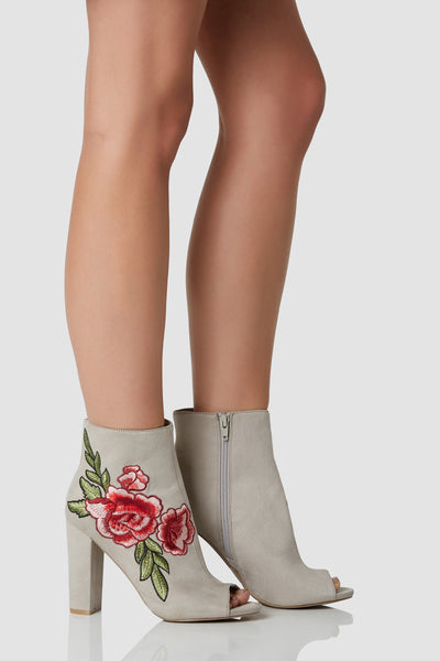Chic pair of above the ankle booties with soft suede like finish. Peep toe design with chunk block heels and intricate rose embroidery.
