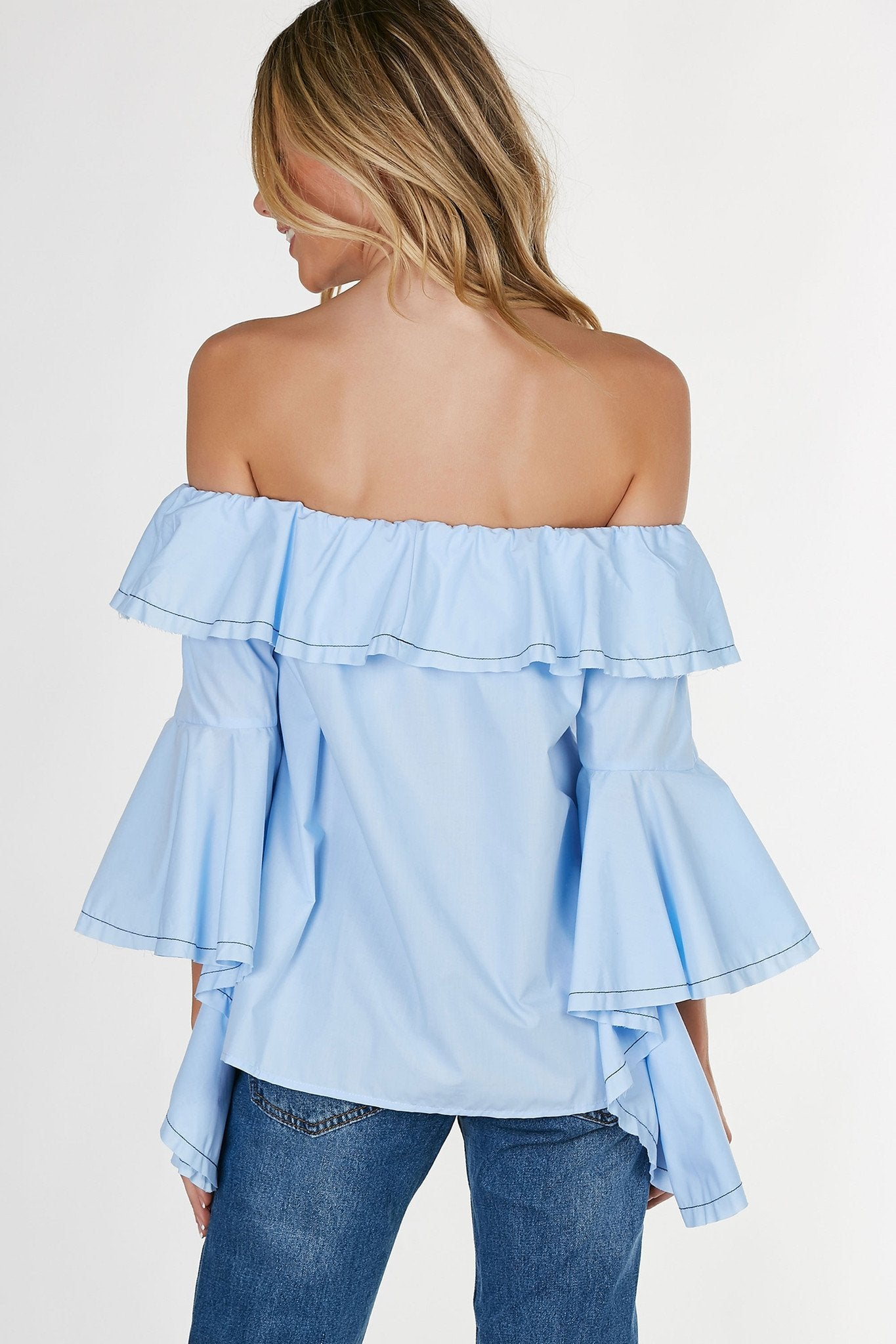 Flirty off shoulder blouse with ruffle tier at neckline. Flared, bell sleeves with contrast seamwork at hem all around.