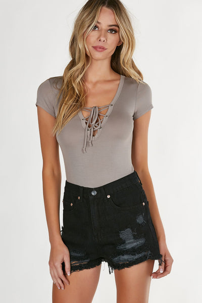 Deep V-neck T-shirt bodysuit with lace up design. Comfy fit with slightly cheeky cut and snap button closure at bottom.