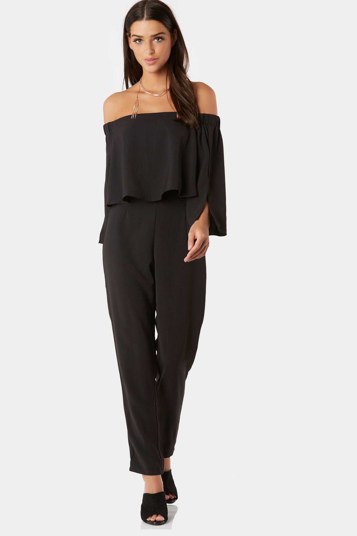 Chic off shoulder jumpsuit with tiered design. Cropped sleeves with slit detailing and back zip closure.